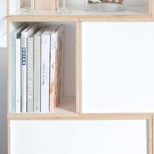 Detail of the BrickBox Small module. You can see the edges of birch plywood. Books, glasses and glasses are stored on this shelf.