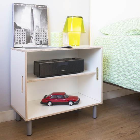 Habitación con mesita de noche formada por una caja de madera BrickBox XL Grande y un estante. Con cuatro patas de metal.
