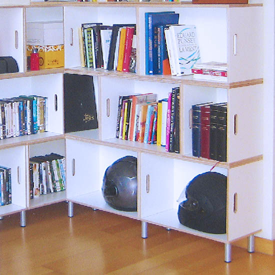 Modular shelving built in corner with metal legs as support. Books and motorcycle helmets are stored.