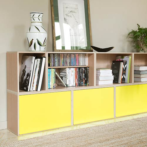 Low modular cabinet with yellow metal doors in the lower row to safeguard the contents of the modules. Oak wood full of books and records.