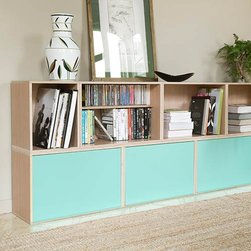 Low modular furniture in a living room. Two-story and with green aluminum doors on the lower floor. With shelves full of books and CDs.
