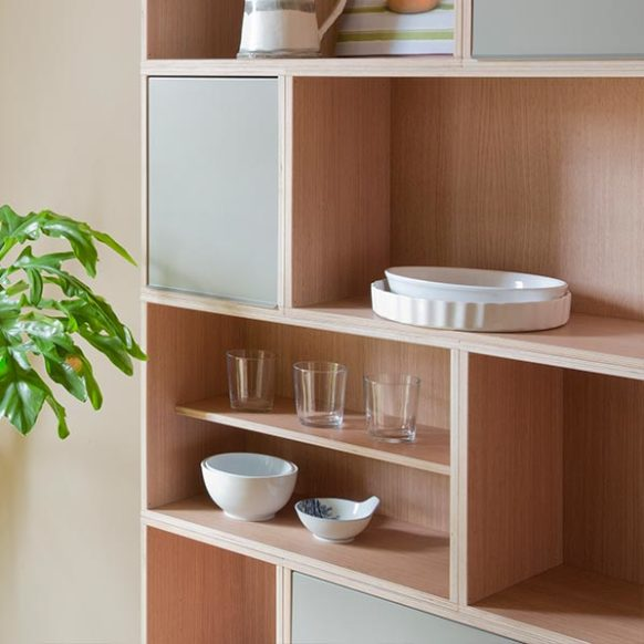 Shelves to store household items in oak. Glasses and plates with wooden shelves. There are also gray doors that protect the content.