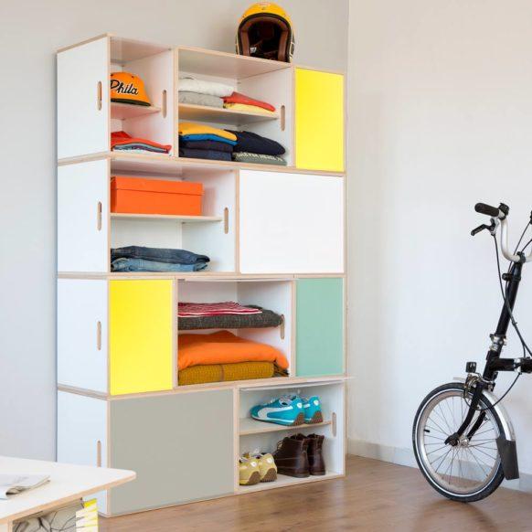 Armario modular blanco de madera contrachapada de abedul. Con puertas de aluminio en cuatro colores, verde, amarillo, blanco y gris. Con estantes para guardar calzado y separar camisetas.