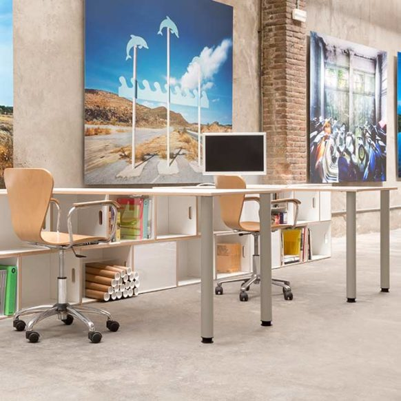 Modern office desks formed by a large white birch plywood board with metal legs and modular shelves in the form of a leg.