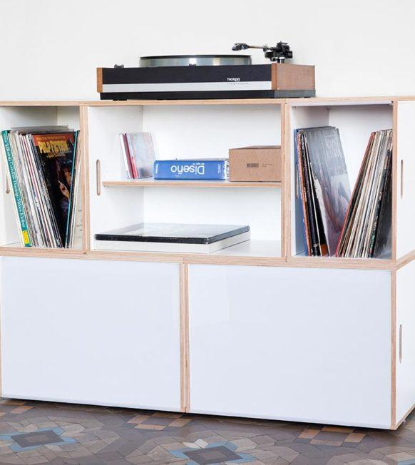 Mueble de almacenamiento de discos de vinilo con tocadiscos apoyado en el piso superior.