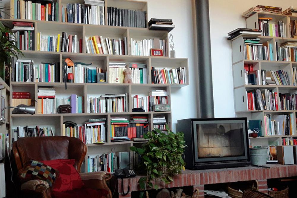 Estanteria para lectura al lado de la chimenea