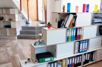 Estanteria BrickBox como mueble bajo escalera y separador de ambientes en una oficina